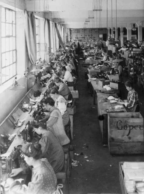No photos of the Lion Shoe Company are known to be in existence but the conditions inside Lion Shoe were likely similar to those in this unidentified shoe factory. In 1921, there were 1,505 manufacturers of shoes and boots. That year 69.5 million pairs of shoes and boots were made for men and 101.5 million pairs for women.<a href=