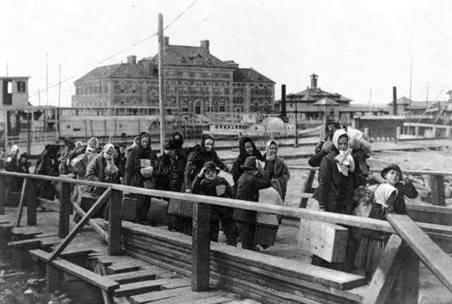 Barges transported immigrants from their steamship company's dock to Ellis Island. Immigrants then walked from the barges to the main building on Ellis Island. In the background is a hospital where ill passengers were dispatched. Credit: Created 1902 Unidentified photographer. Library of Congress, Prints and Photographs Division [reproduction number LC-USZ62-12595].