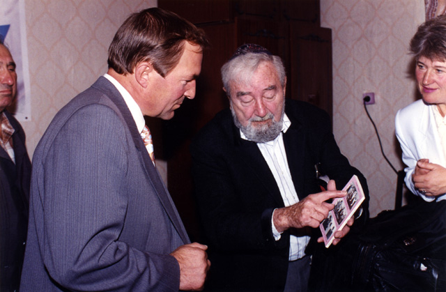 Baruch showing a book to the mayor of Novograd Volynsk, Vladimir Ivanovich Zagrevy. The middle-aged woman looking on is in charge of providing human services to the elderly Jews in the community.