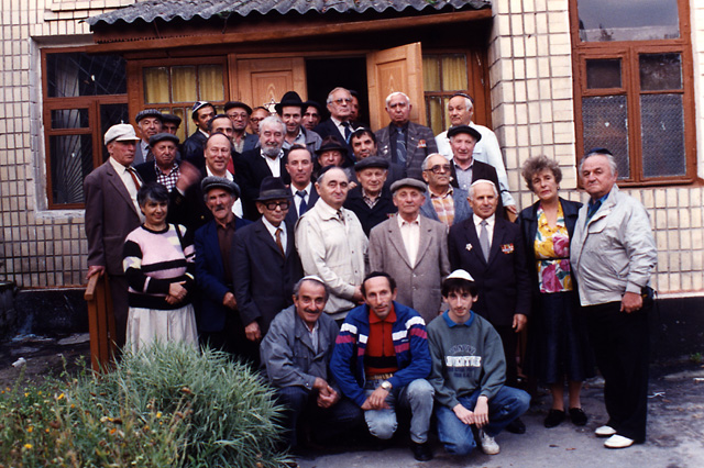 Paul Gass and Baruch Korff posing for a photo with some of the members of the Jewish community of Novograd Volynsk